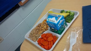 School lunch tray with milk, carrots, chicken, rice, banana, and broccoli